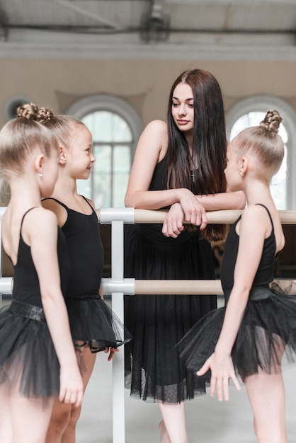 Ballerina girls with their instructor in dance studio Free Photo