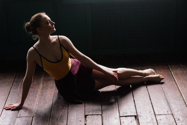 Балерина в темном боди, в платье в темном интерьере ателье. стена из кирпича, пианино. Premium Фотографии