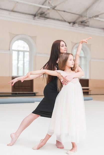 Ballerina instructor and girl poising in dance studio Free Photo