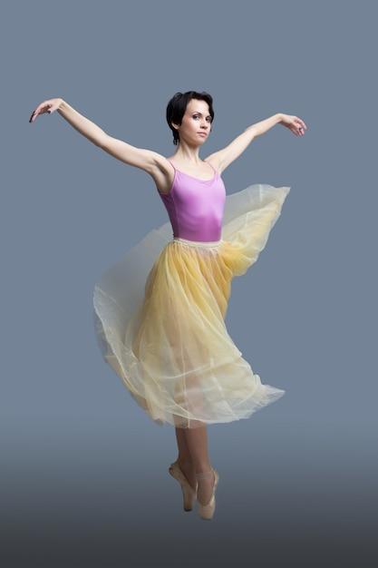 Ballerina is dancing on a gray Premium Photo