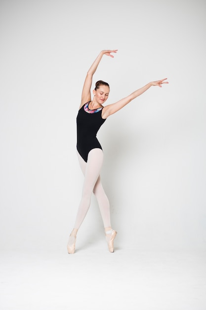 Ballerina is standing in a dancing pose on pointes on a white background Premium Photo