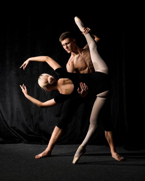 Ballerina in posa con l'uomo che tiene la sua gamba Foto Gratuite