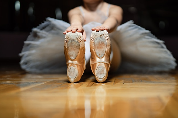 Ballerina sitting on the floor of classroom and and holding for tiptoes of white ballet shoes on the wooden floor. classic ballerinas' pointes of a small girl . close-up Premium Photo