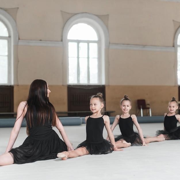 Ballerina teacher looking at three girls stretching on floor Free Photo