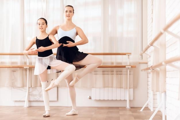 Ballerina teaches little girl at ballet school. Premium Photo