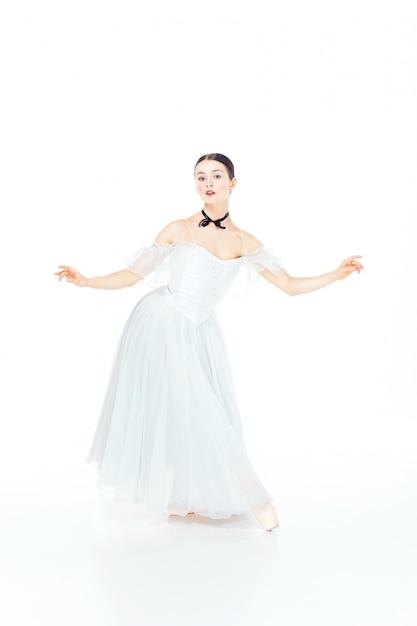 Ballerina in vestito bianco che posa sulle scarpe del pointe, bianco dello studio. Foto Gratuite
