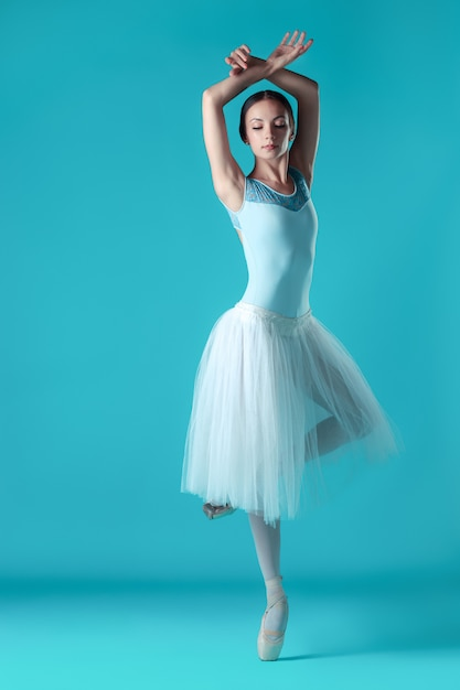 Ballerina in white dress posing on toes Free Photo