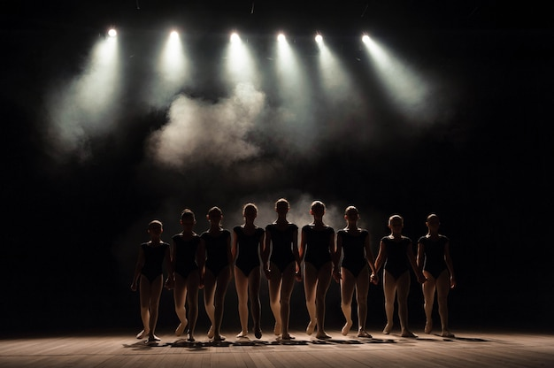 Ballet class on the stage of the theater with light and smoke. children are engaged in classical exercise on stage. Premium Photo