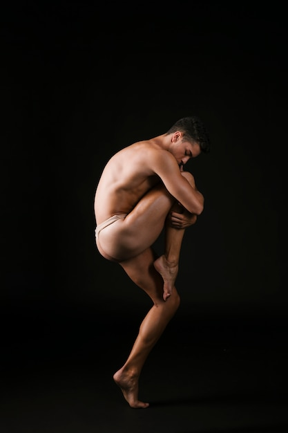Ballet dancer embracing knee passionately Free Photo