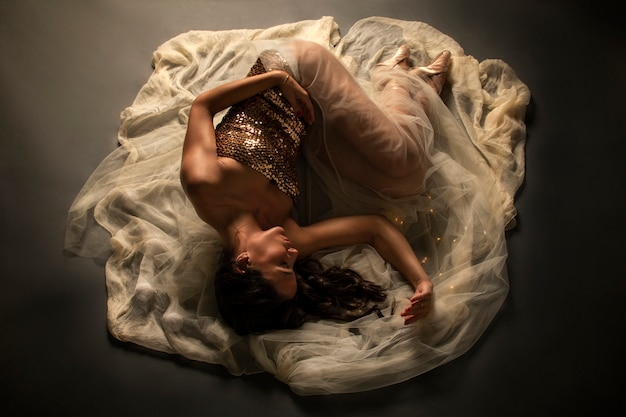 Ballet dancer on the floor on a veil Premium Photo