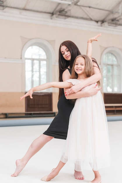 Ballet dancer hugging smiling cute girl practicing in dance studio Free Photo