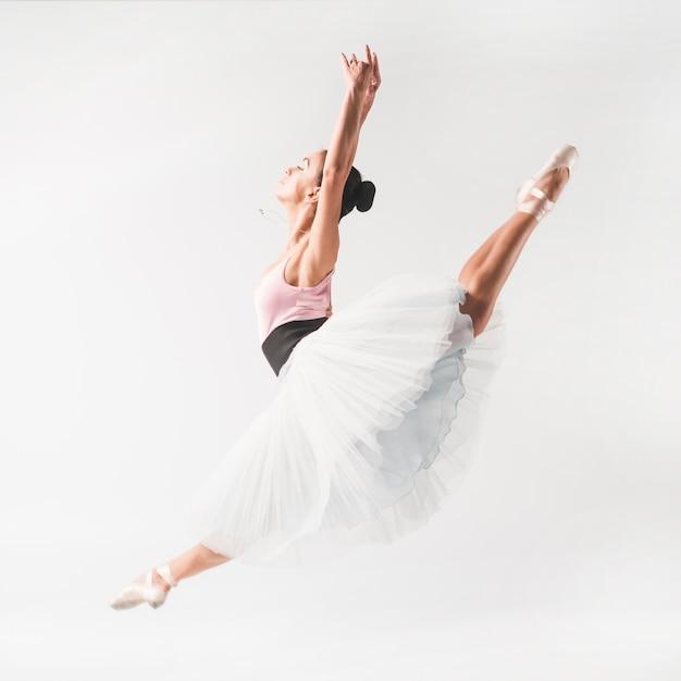 Ballet dancer wearing tutu posing in front of white backdrop Free Photo