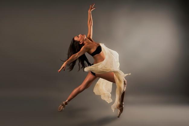 Балерина в черном белье и марле, покрывающей ее, делает танцевальную позу Premium Фотографии