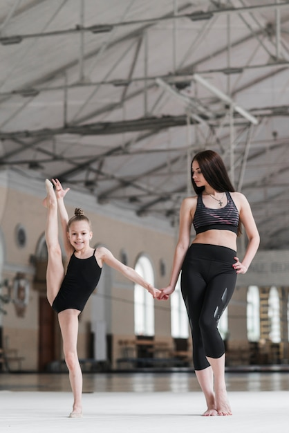 Ballet instructor holding young ballerina's hand in dance class Free Photo
