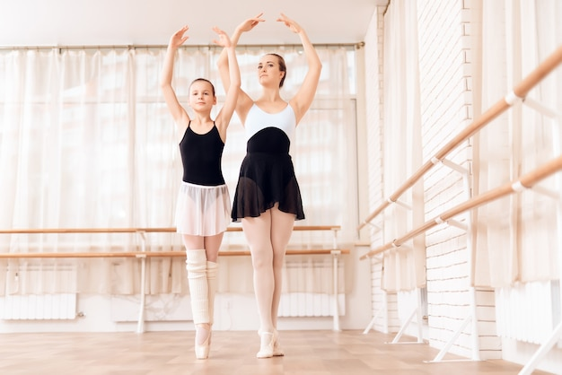 Ballet teacher trains kid at dance school. Premium Photo