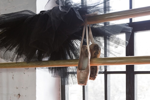 Ballet tutu and pointe shoes in the rehearsal room. old pointe shoes. Premium Photo