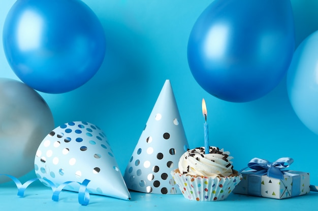 Balloons, birthday hats, cupcake and gift box on blue background, close up Premium Photo