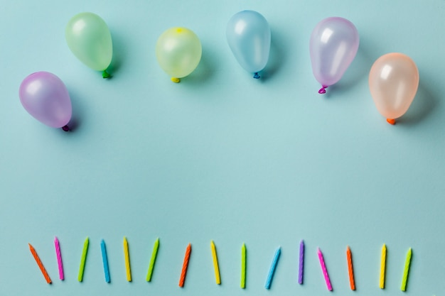Balloons over the row of colorful candles against blue background Free Photo