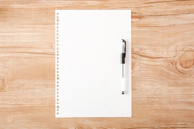 Шариковая ручка прикреплена к пустой вкладышу на деревянном столе Premium Фотографии