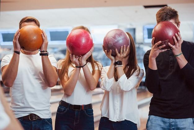 Palline con numeri diversi sopra. i giovani amici allegri si divertono al bowling durante i fine settimana Foto Gratuite