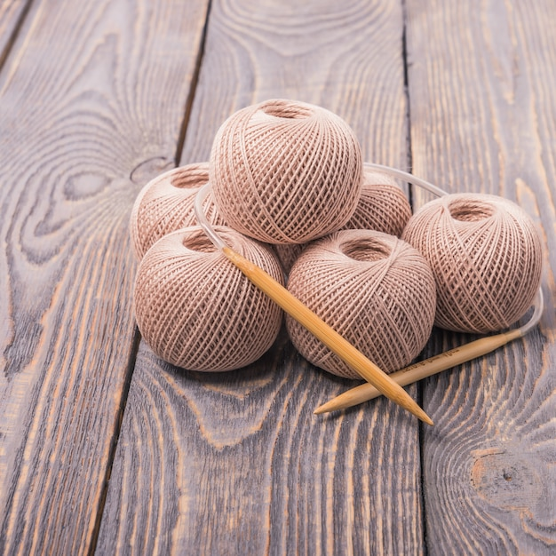 Balls of yarn and knitting needles for knitting on a wooden background. Premium Photo
