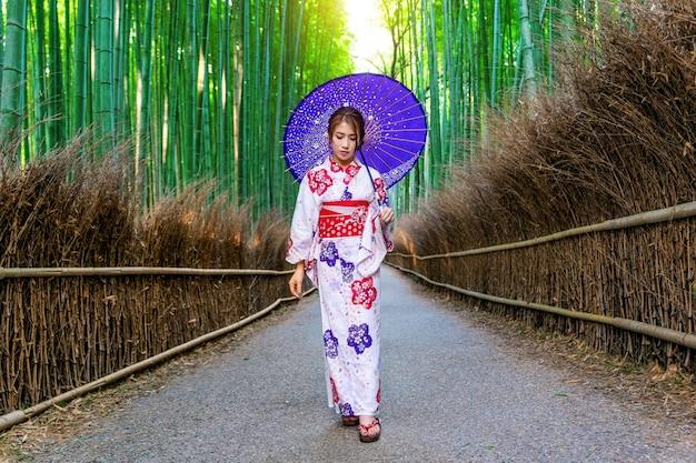 竹林。日本の京都の竹林で日本の伝統的な着物を着ているアジアの女性。 無料写真