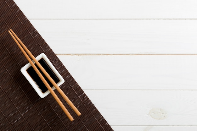 Bamboo Mat And Soy Sauce With Sushi Chopsticks On White