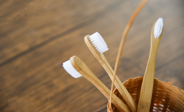 Bamboo toothbrush in basket eco natural plastic free items on rustic background Premium Photo