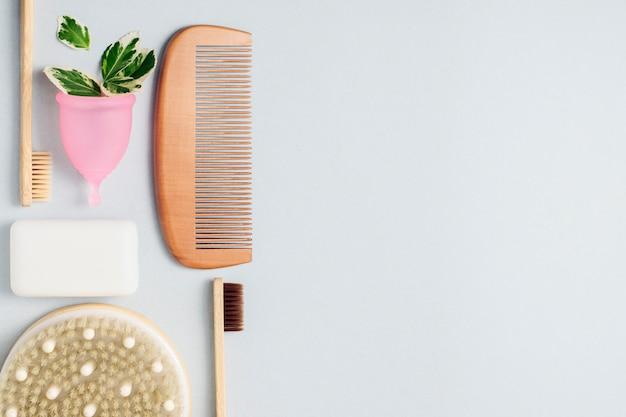 Бамбуковые зубные щетки, менструальная чашка, расческа для волос, мыло на сером фоне с копией пространства. ноль отходов концепция, повторное использование. Premium Фотографии