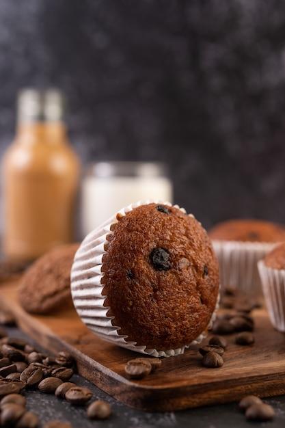 コーヒーの穀物が付いている木の皿に置かれるバナナのカップケーキ。 無料写真