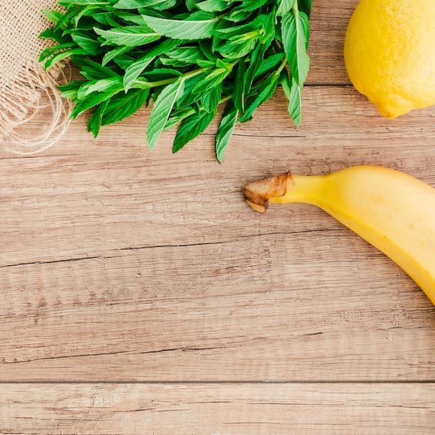 Banana, lemon and mint on table Free Photo