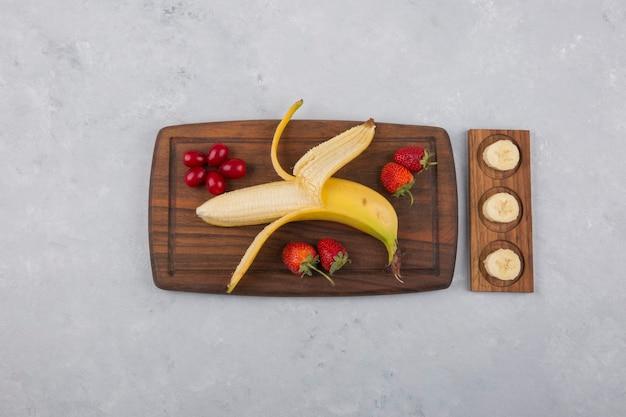 Банан, клубника и ягоды на деревянном блюде посередине Бесплатные Фотографии