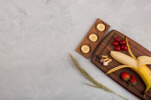 Банан, клубника и ягоды на деревянном блюде Бесплатные Фотографии