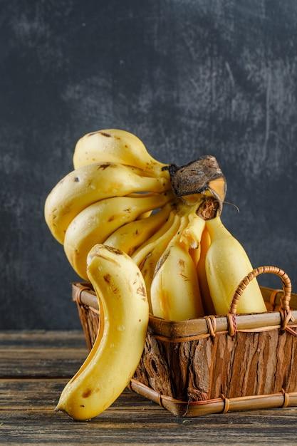 Бананы в корзине на деревянном и гипсовом. Бесплатные Фотографии