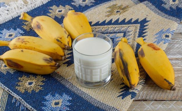 Бананы с молоком под высоким углом на деревянном и килим ковре Бесплатные Фотографии