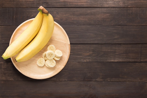 Bananas in a wooden dish on a wooden background. space for text Premium Photo