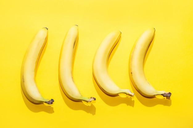Bananas on yellow pastel background. minimal idea food concept Premium Photo