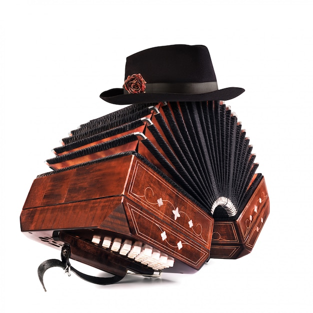 Bandoneon, tango instrument with a male hat on top on white Premium Photo