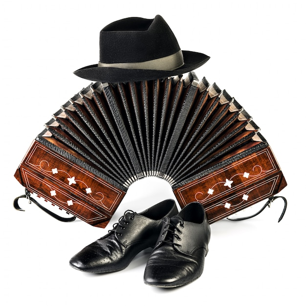 Bandoneon, tango shoes and a black hat isolated on white Premium Photo