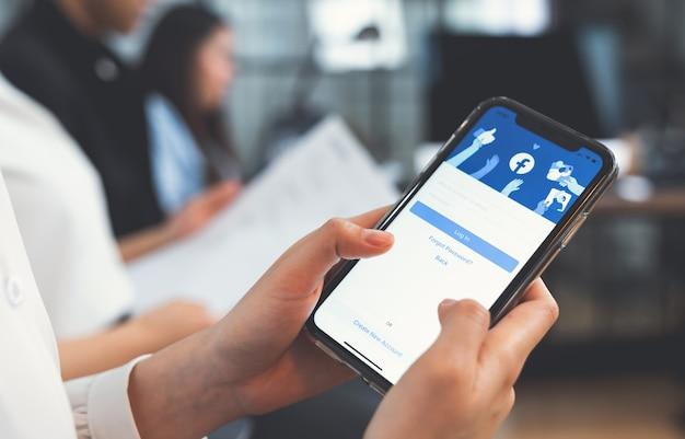 Бангкок, таиланд - 6 апреля 2020 года: женщина рука нажимает на экран facebook на apple iphone, социальные медиа используют для обмена информацией и сетей. Premium Фотографии