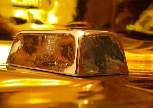 Банк золотой слиток на золотой поверхности Premium Фотографии