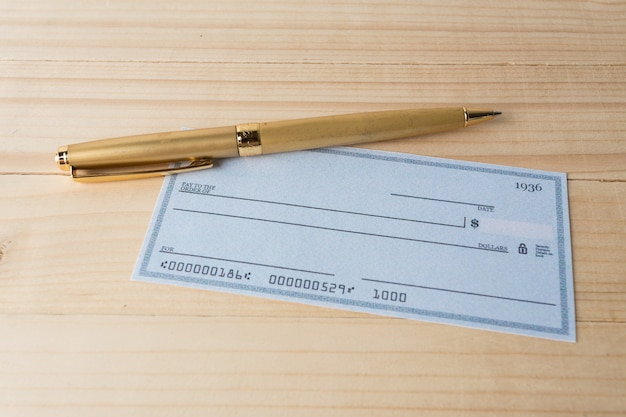 Banking check with magnifier glass Premium Photo