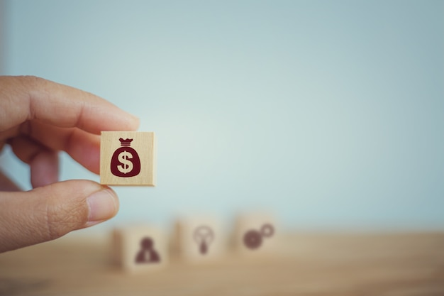 Banking and finance, financial planning concept: hand chooses wooden cube blocks with us dollar bags icons. management of corporate money to be consistent with the income in each quarter. Premium Photo