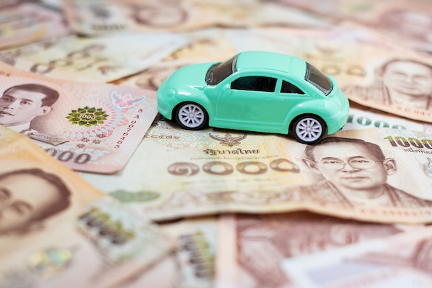 Banknote stack with car and calculator. Premium Photo
