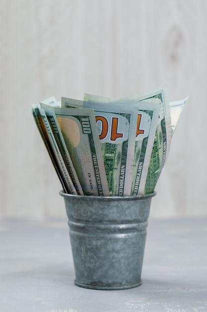 石膏と木製のテーブルにミニバケツの紙幣 無料写真