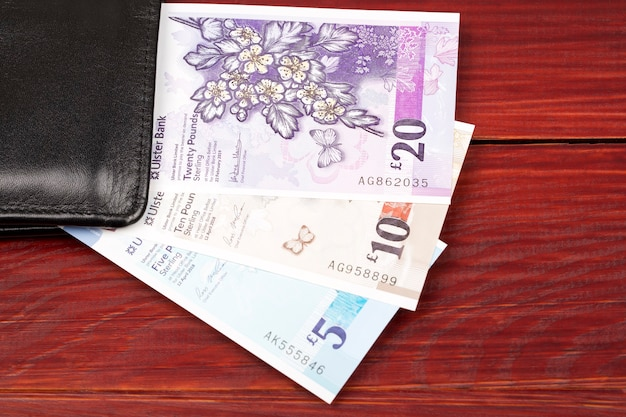 Banknotes of northern ireland in the black wallet Premium Photo