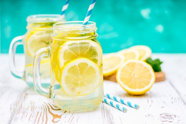 Banks with handles with cold lemonade on a white wooden background. lemons. Premium Photo
