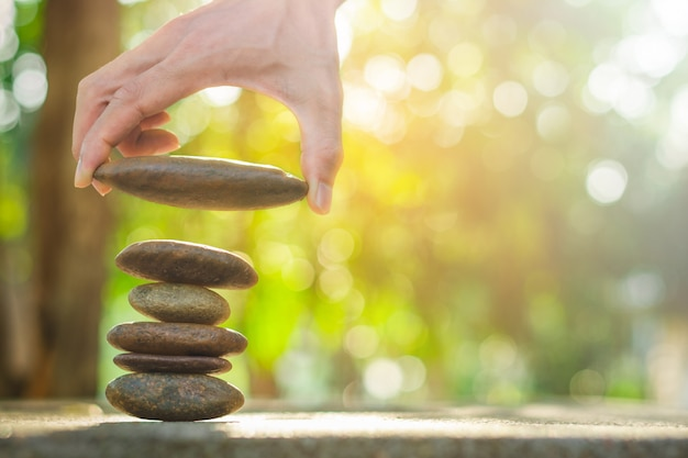 Banlance stones for spa with hand holding stone on abstract bokeh background Premium Photo