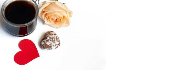 バナーコーヒー、ハートの形をしたチョコレートケーキ、白い背景の上の黄色いバラ、コピースペース Premium写真