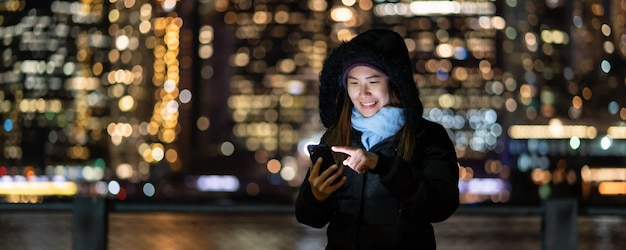 Banner and cover of asian woman in winter suit using smart mobile phone with smile action Premium Photo